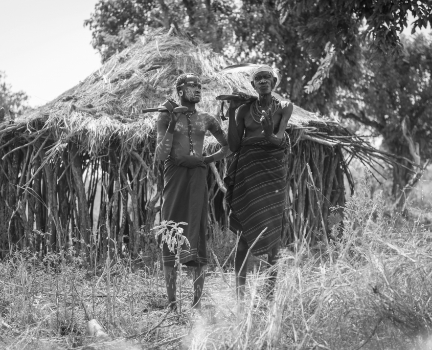 unidentified Mursi men in front of a hut with weapons in their hands. Mursi use guns for wild animals and against opposing tribes B&W