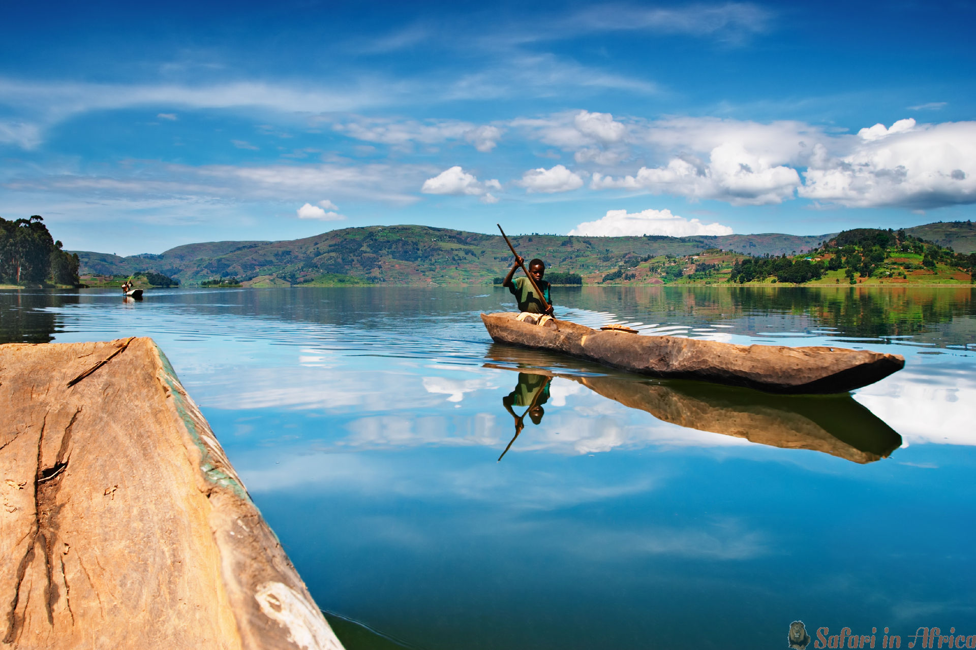 African boy in canoe, Bunyonyi lake, Uganda