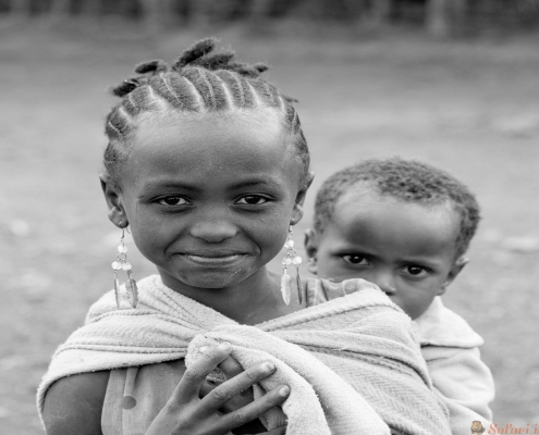 Carrying brother in Ethiopia, Oromia B&W