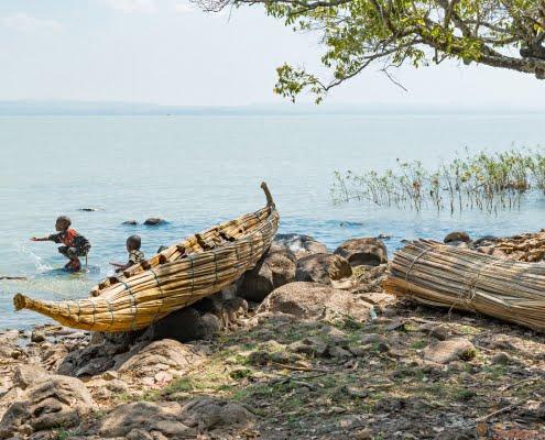 Children playing in the Tana lake niar a reed canoe bahir dar
