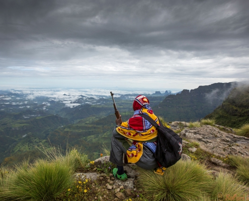 Ethiopian mountain guide resting and overlooking the valley. Simien Mountains