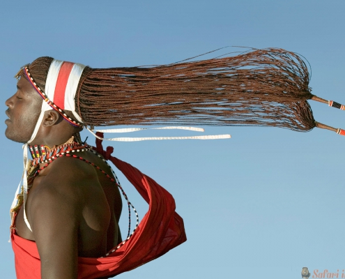 Flying Masai appears to float in air with his hair hanging behind him, Lewa Wildlife Conservancy, North Kenya, Africa