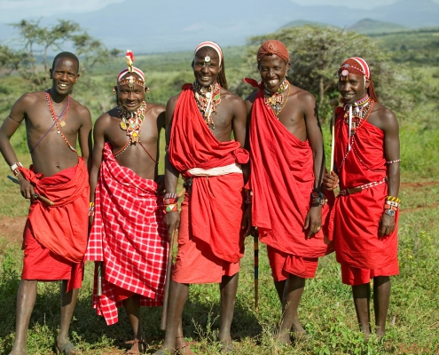 Group portrait of five Masai Warriors in traditional red toga at Lewa Wildlife Conservancy in North Kenya, Africa