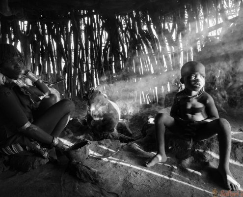 Hamer woman cooking food in her hut with her child near Turmi B&W