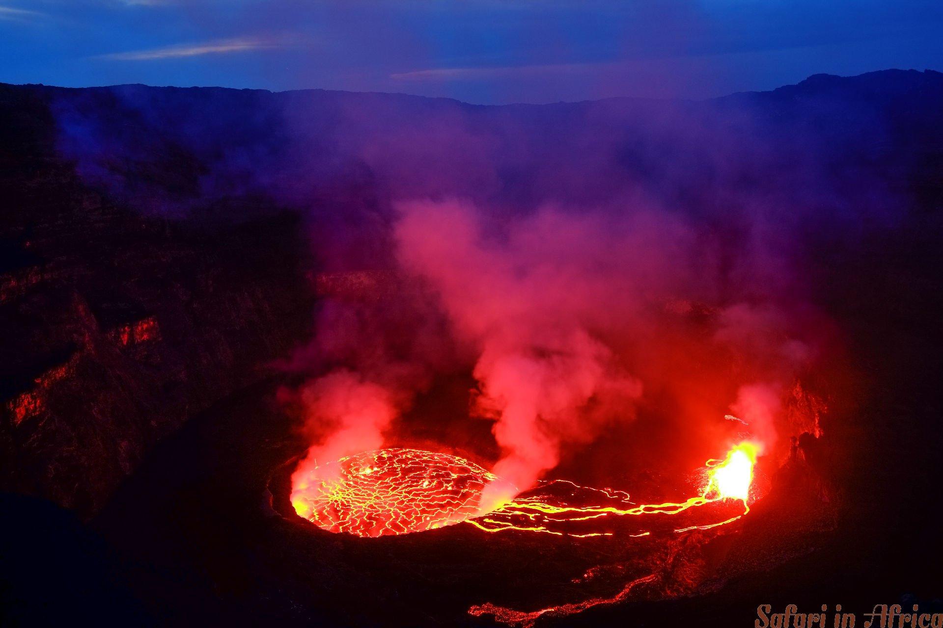Lava en stoom in krater van Nyiragongo-vulkaan in Virunga-natie. Meer, actie