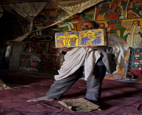 Priest opens an illustrated Bible inside a church in Ethiopia