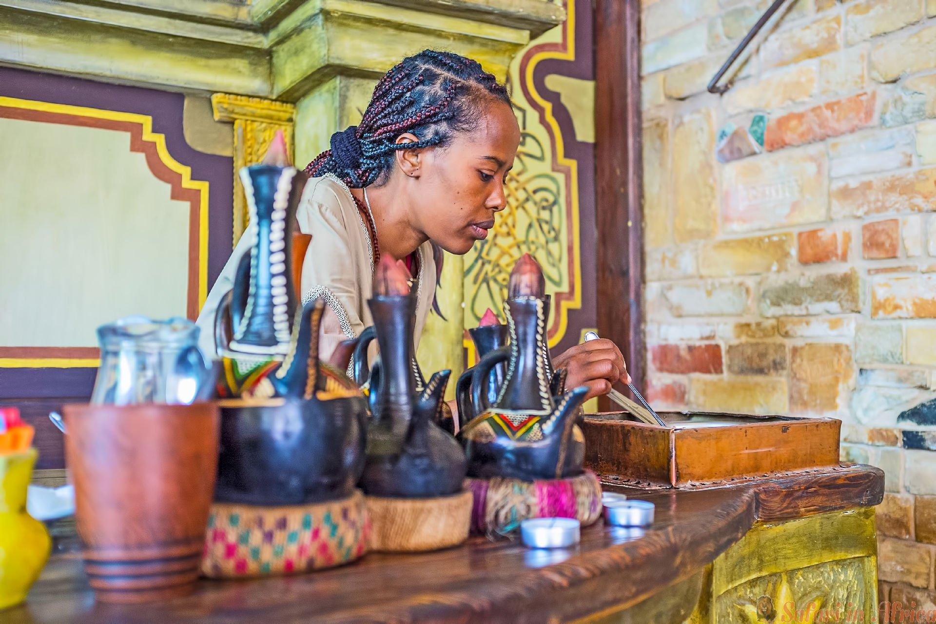 Het jonge Ethiopische Tigrayan-meisje op het werk - ze braadt koffiebonen voor de traditionele koffieceremonie