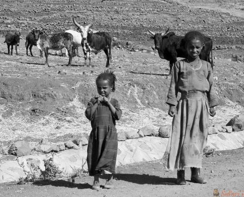 Two unidentified sisters hesitate to cross the road in Ethiopia axum B&W