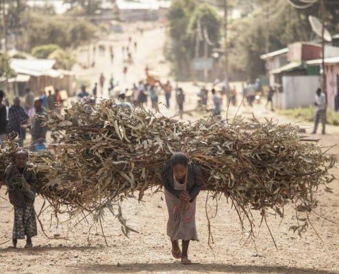 Vrouw en kind met zware ladingen, Ethiopië